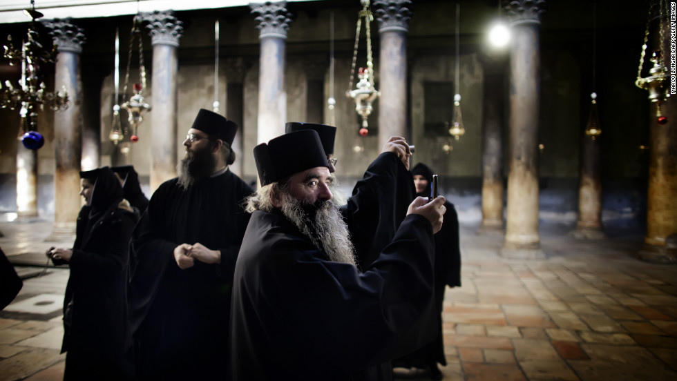 Orthodox monks tour the Church of the Nativity in Bethlehem, situated in the West Bank near Jerusalem. Palestinian authorities fear that visitor numbers will be lower than usual this Christmas, following a spate of cancellations due to violence in Gaza.