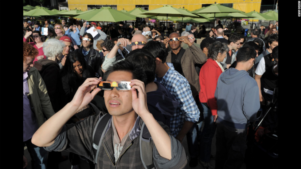 Observers in New York's Riverside Park view the event through special cardboard glasses.