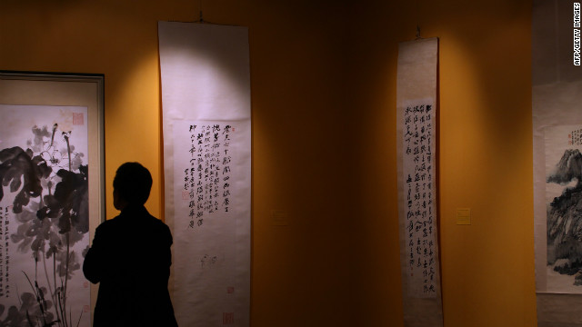 A man looks at artworks on display during a Christie's spring auction preview in Hong Kong on May 24, 2012.