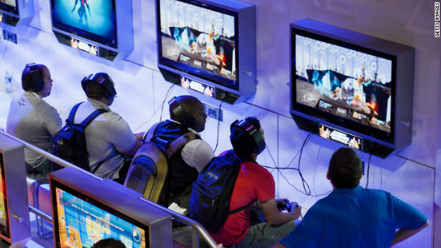 Attendees play new video games at the Sony PlayStation booth this week during the E3 gaming conference.