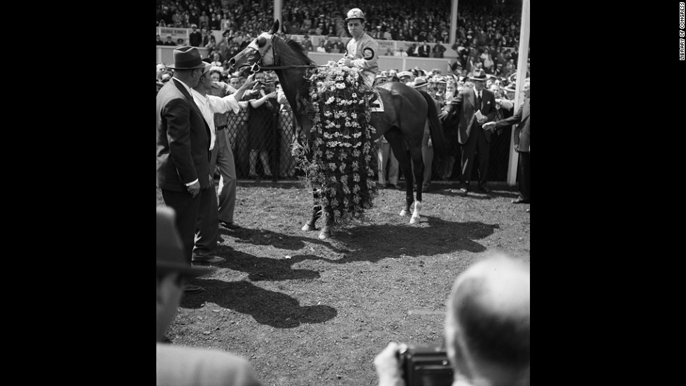 Count Fleet, who won the Triple Crown in 1943, is adorned with flowers after winning the Preakness that year.