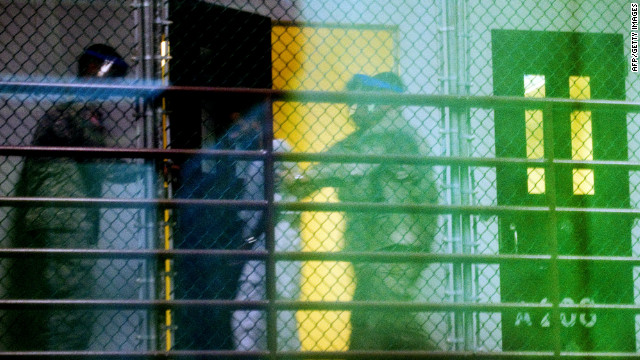 This image, reviewed by the U.S. military and shot through a one-way mirror, shows guards moving a detainee from his cell at Guantanamo Bay, Cuba, in January.
