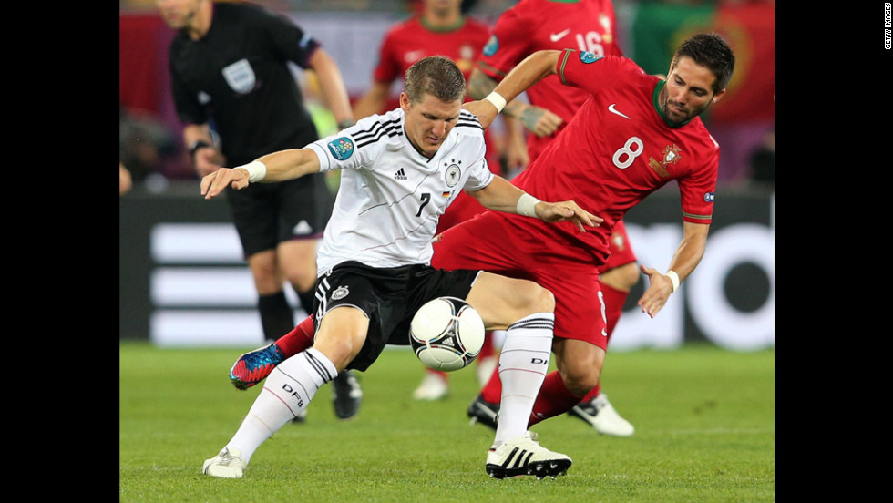 Bastian Schweinsteiger of Germany holds off a challenge from Joao Moutinho of Portugal.