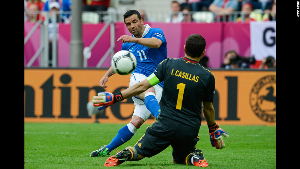 Italy's Antonio Di Natale kicks the ball past goalkeeper Iker Casillas of Spain.