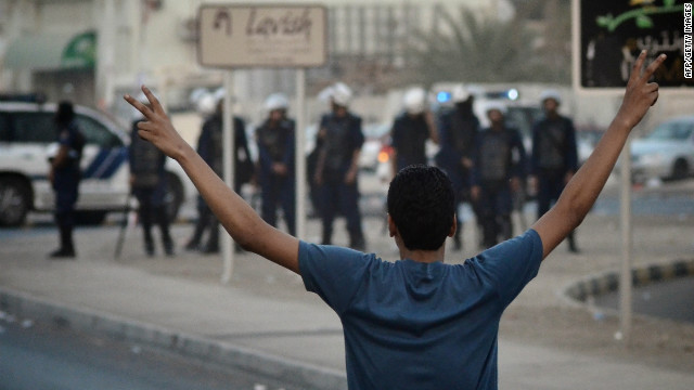 A Bahraini protester flashes a 'V' sign for victory in front of riot police during a June anti-government demonstration in Bahrain.