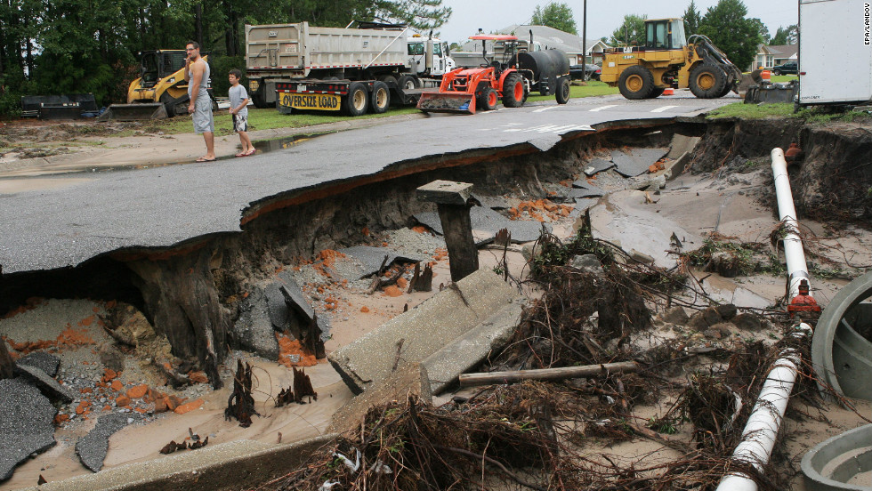 The downpour leaves a Pensacola road washed out as Will Tollis, left, and his son Micah, 9, check out the damage Sunday, June 10. Authorities also warned of rip currents that could endanger anyone entering the surf along the Alabama and Florida coasts through Monday afternoon, June 11.