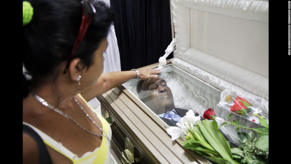 A woman touches the coffin of Cuban boxing great Teofilo Stevenson on Tuesday in Havana, Cuba. The three-time Olympic gold medalist died Monday.