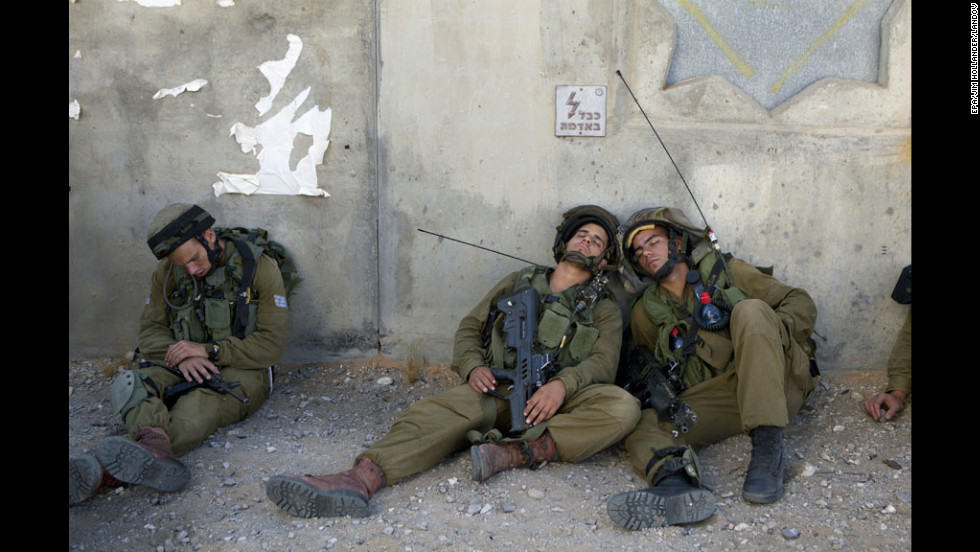 Israeli infantry soldiers catch a short nap in the shade of a wall Tuesday in the army's urban warfare training base outside Ze'elim, southern Israel.