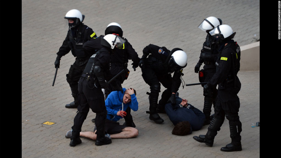 Polish riot police in Warsaw detain football fans Tuesday before the Euro 2012 championships match between Poland and Russia.