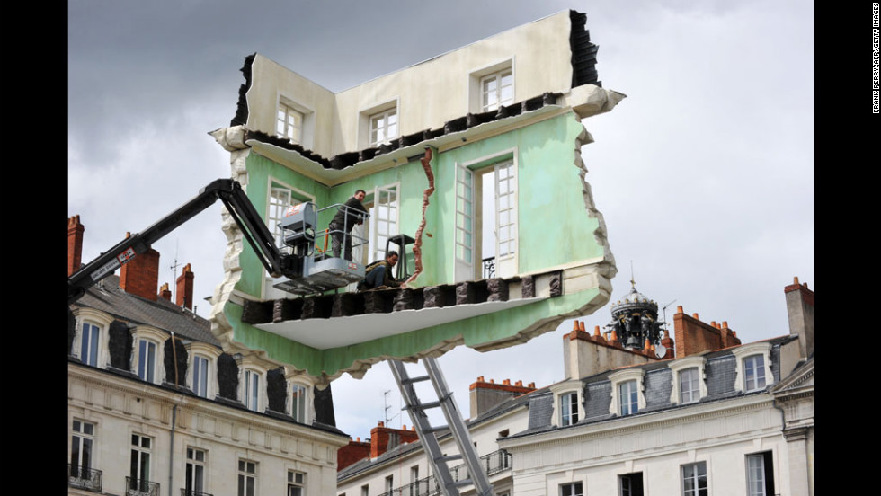 "Workers put the final touches on an installation by Argentine artist Leandro Erlich on Wednesday in Nantes, France. It is part of ""Le voyage a Nantes,"" a contemporary art event in 40 stages along Nantes streets."