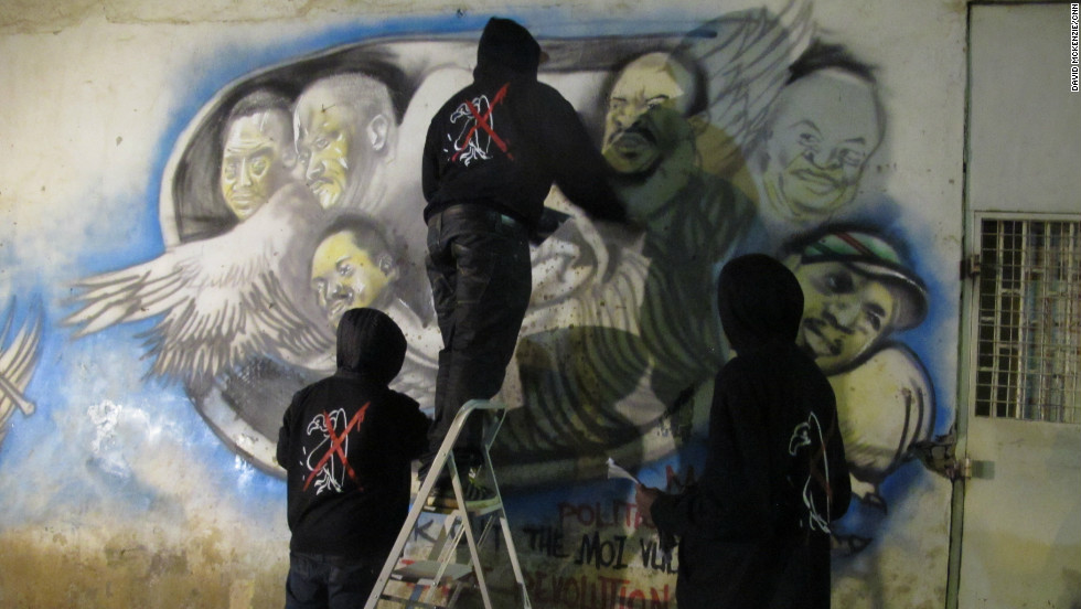 Graffiti artists work on the details of their latest piece in Nairobi, Kenya. They paint political art highlighting corruption and compare national leaders to vultures.