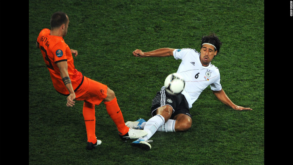 John Heitinga of the Netherlands and Sami Khedira of Germany compete for the ball during the Group B match between Netherlands and Germany.