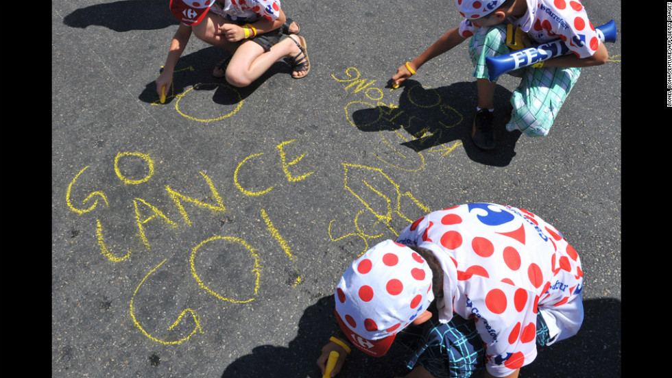 Young Armstrong fans write messages on the ground using yellow chalk ahead of the 2009 Tour de France. He came third that year.