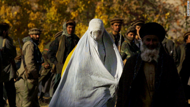 A woman wearing a traditional burqa flees the village of Khanabad U.S. warplanes drop bombs on Taliban positions in 2001.