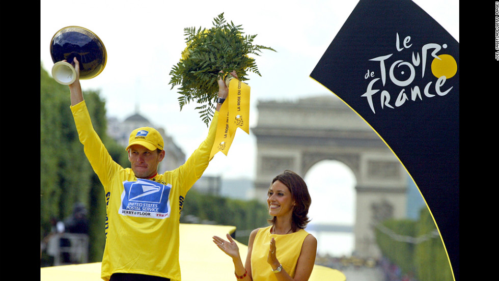 Armstrong celebrates on the podium after winning the Tour de France by 61 seconds in 2003.