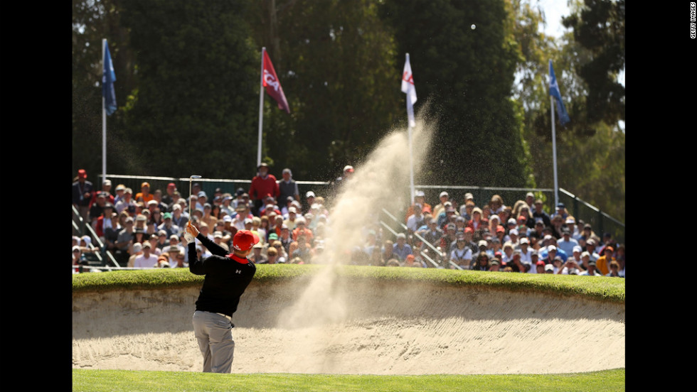 Hunter Mahan of the United States plays a bunker shot on the 17th hole during the first round.