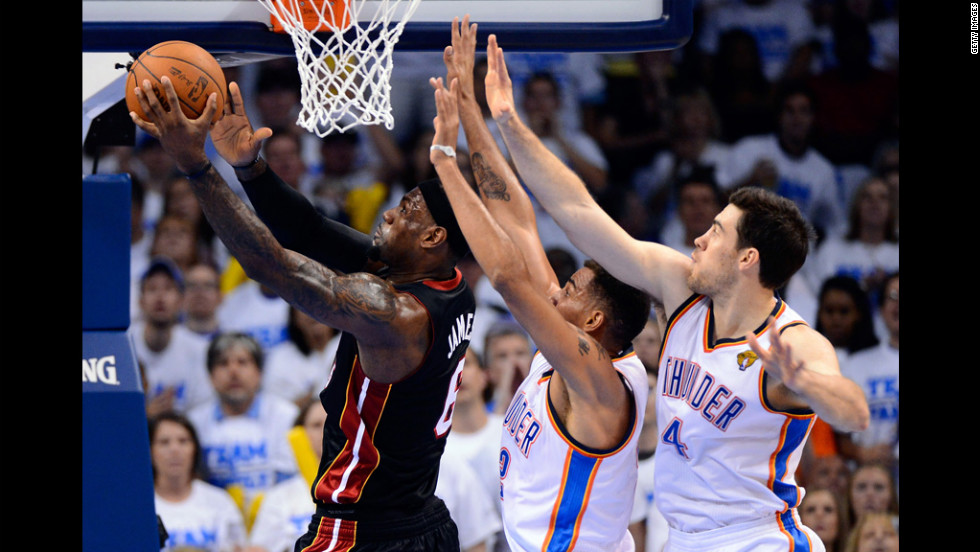 The Miami Heat's LeBron James fires up a shot against the Oklahoma City Thunder's Nick Collison and Thabo Sefolosha, right, during the first quarter.