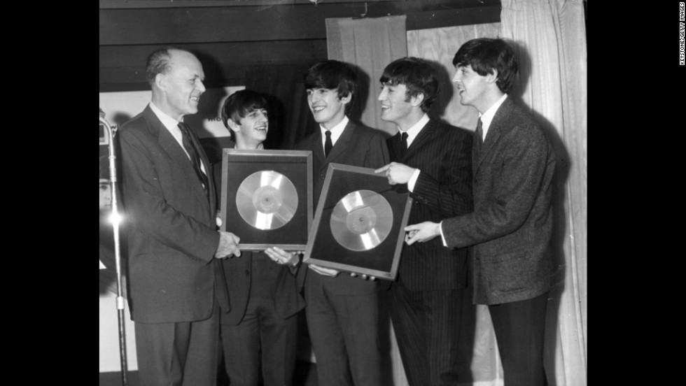 "Sir Joseph Lockwood, chairman of EMI Music, presents The Beatles with two silver records for their albums ""Please, Please Me"" and ""With The Beatles,"" which reached 250,000 sales."