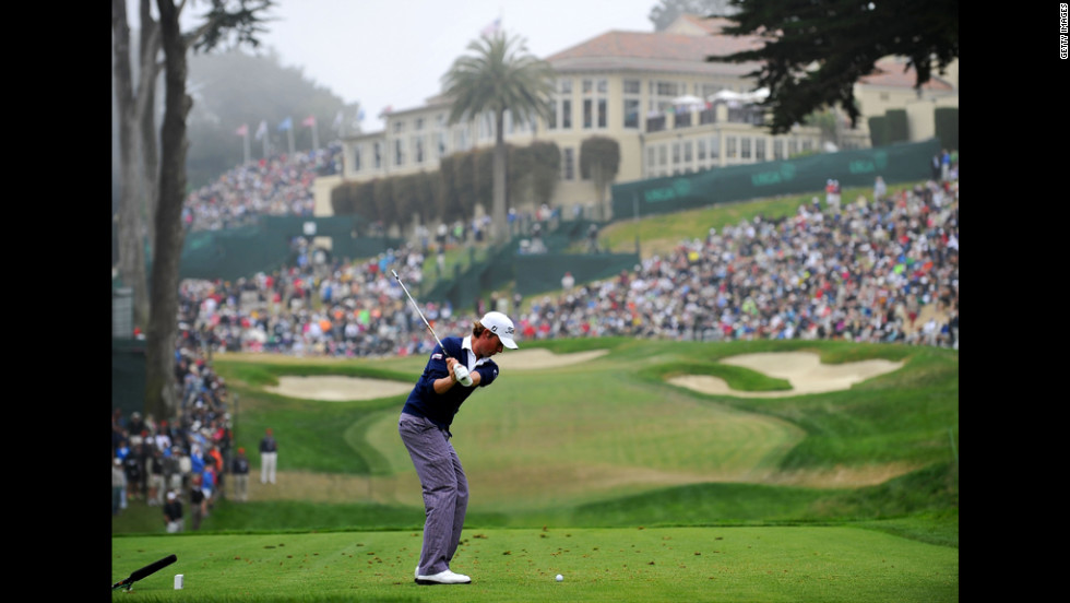 Webb Simpson of the United States hits his tee shot on the eighth hole.