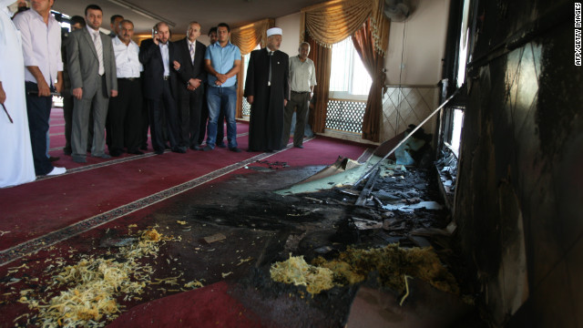 Palestinians from the village of Jabaa look at damage at a mosque which was partially set on fire overnight on June 19, 2012.
