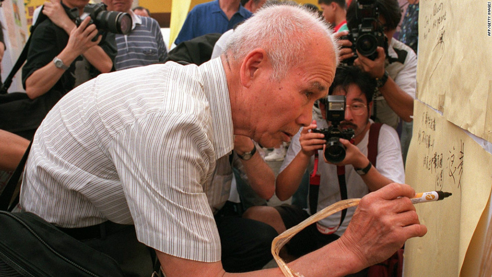 An elderly Hong Kong man signs an anti-communist board during a demonstration by activists of the Hong Kong Democratic Party on June 28, 1997.  Some residents feared democratic rights and freedoms would be eroded in Hong Kong under Chinese rule.