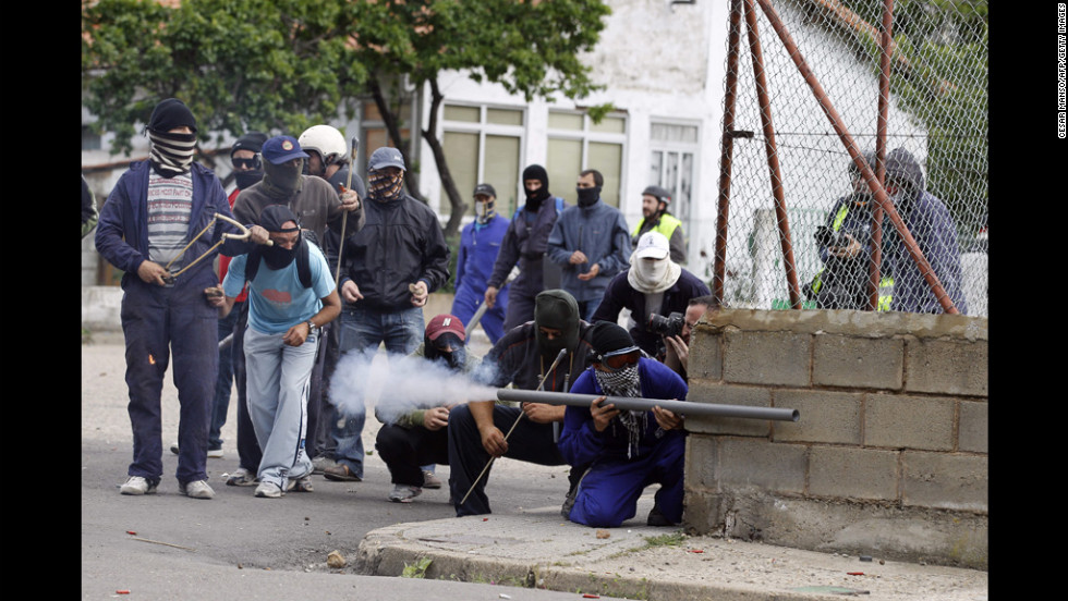 Miners fire homemade rockets Tuesday toward civil guards in Cinera, Spain, during a mass strike against subsidy cuts that the miners say threaten tens of thousands of jobs.