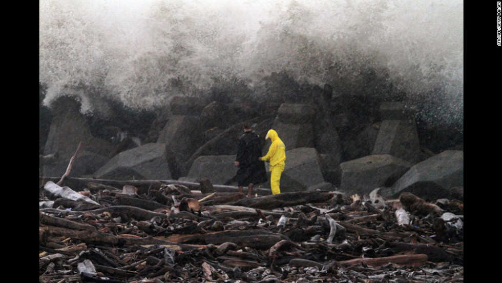 Two local residents pick up driftwood as waves crash against the coast Wednesday in Chung-yun fishing harbour in Kaohsiung, Taiwan.