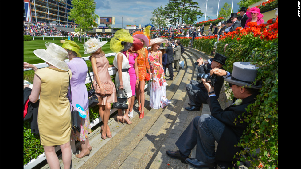 Photographers in top hats snap photos of Royal Ascot attendees.