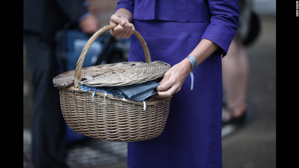 A dress code assistant holds a basket of pashminas at the main entrance to Royal Ascot. Visitors are expected to keep to a strict dress code.