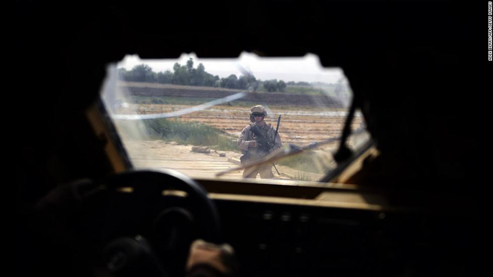 A photo taken from a inside a Mine Resistant Ambush Protected vehicle shows a U.S. Marine standing outside Patrol Base Toofan before a shura meeting Thursday at Bahlul Khan village in Afghanistan's southern Helmand province.