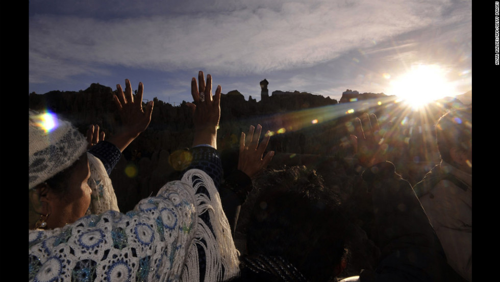 Aymara natives raise their hands at sunrise Thursday to receive the first sun rays during the celebration of the winter solstice, which marks the Aymara New Year, at the Valley of the Moon, near La Paz, Bolivia.