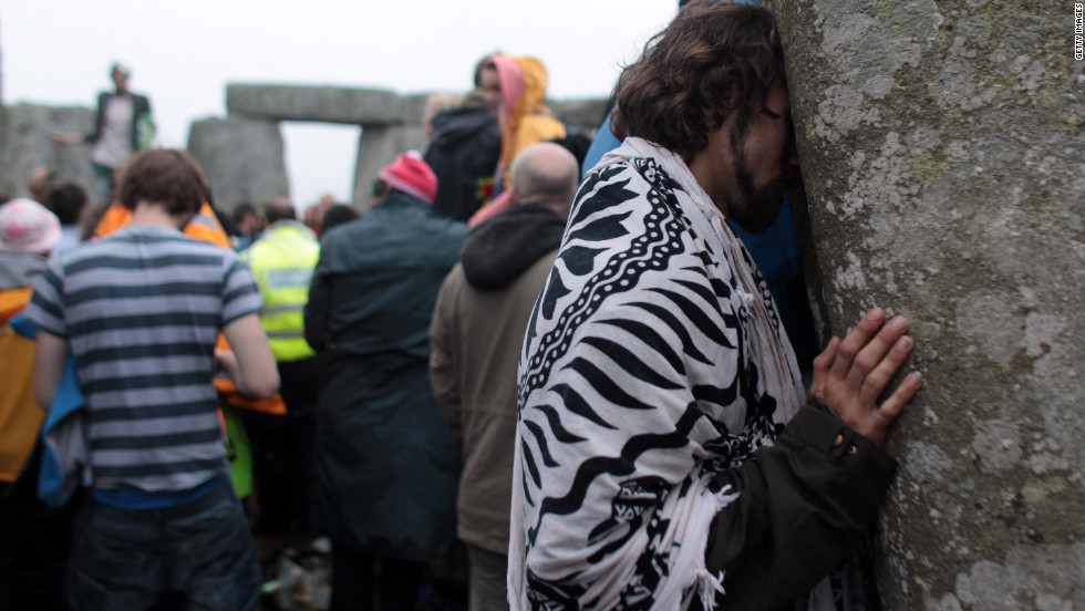 A man rests his head on a stone at Stonehenge, which many consider a holy site.