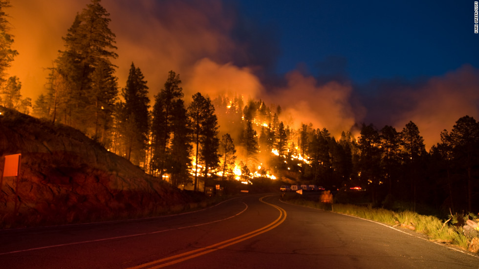Flames turn night into day along a road this month during New Mexico's Little Bear Fire at Lincoln National Forest.