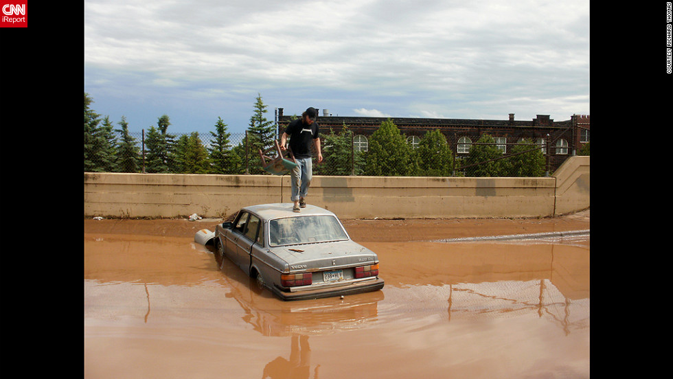 Ian Koivisto drove his car into this flooded area of Dultuh, Minnesota, early Thursday and then had to swim to safety. Richard Thomas, a CNN iReporter, took this photo of Koivisto atop his car.