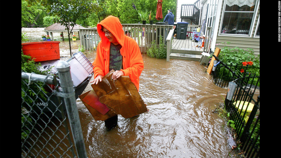 Connie Strong clears debris from her neighbor's yard in Duluth's Lincoln Park neighborhood Wednesday, June 20, after record rainfall. Flood warnings remain in effect for parts of six counties around Duluth.