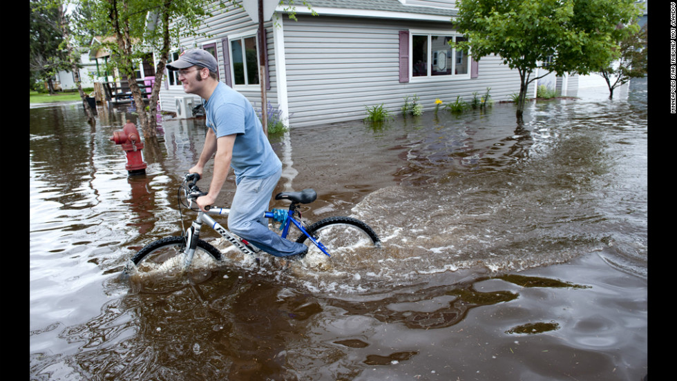 Brytton George rides a bike through flooded streets Wednesday near his home in Carlton. The flooding washed out roads and bridges, causing millions of dollars in damage.