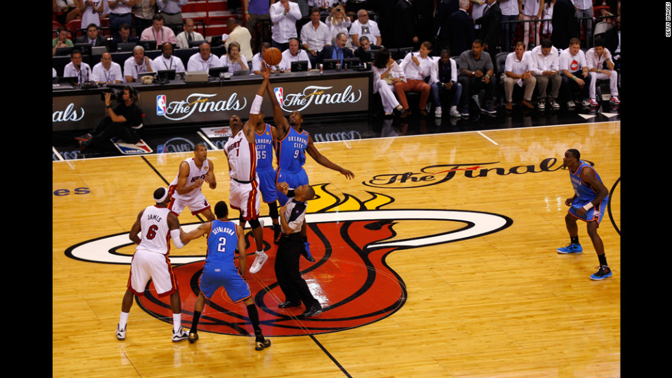 Chris Bosh, No. 1 of the Heat, fights for control of the opening tip-off against Serge Ibaka, No. 9 of the Thunder.
