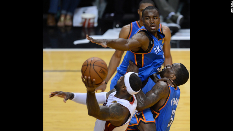LeBron James, left, of the Heat goes to the basket against Serge Ibaka, center, and Kendrick Perkins, right, of the Thunder.