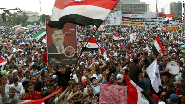 Supporters of Muslim Brotherhood presidential candidate Mohamed Morsi (portrait) rally in Cairo's Tahrir Square on June 23, 2012.