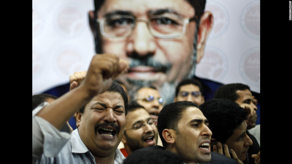 June: Supporters of the Muslim Brotherhood's presidential candidate Mohamed Morsy celebrate in front of his picture at his headquarters in Cairo on June 24. Morsy was declared Egypt's first democratic president.