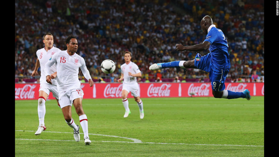 Mario Balotelli of Italy strikes the ball as Joleon Lescott of England looks on.