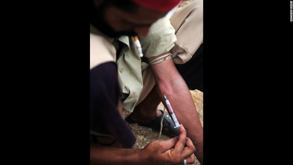 A Pakistani drug addict injects heroin along a street in Karachi on Monday. Pakistan has more than 4 million drug addicts in a population of nearly 180 million, according to figures compiled by the Anti-Narcotics Force.