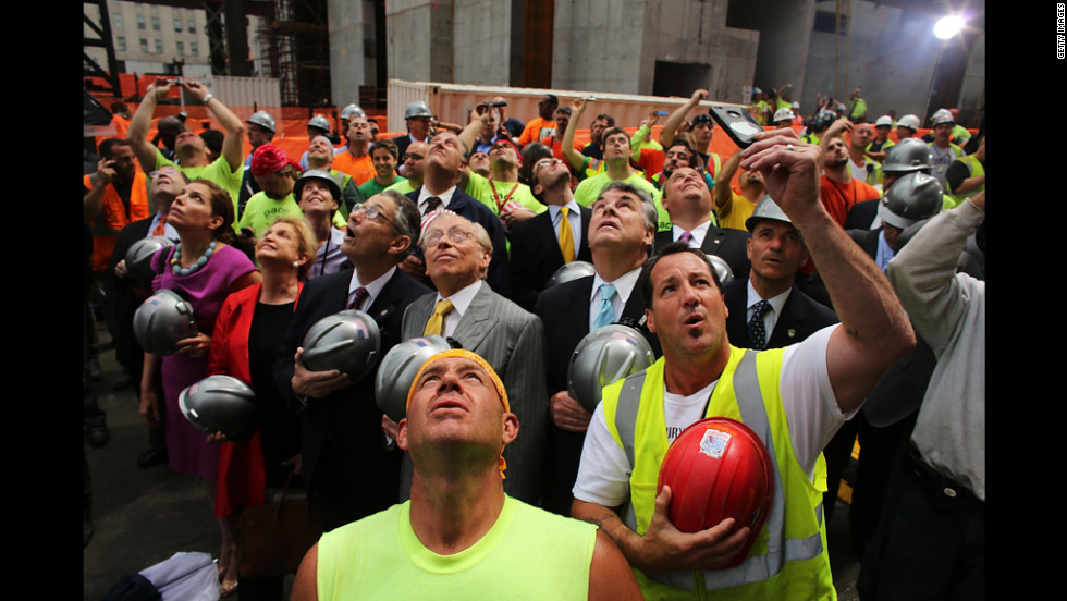 Construction workers, developers and observers watch as the last steel beam, signed by members of the crews that helped build the tower, is hoisted 977 feet to the top of Four World Trade Center in New York on Monday. The building is scheduled to open in 2013.