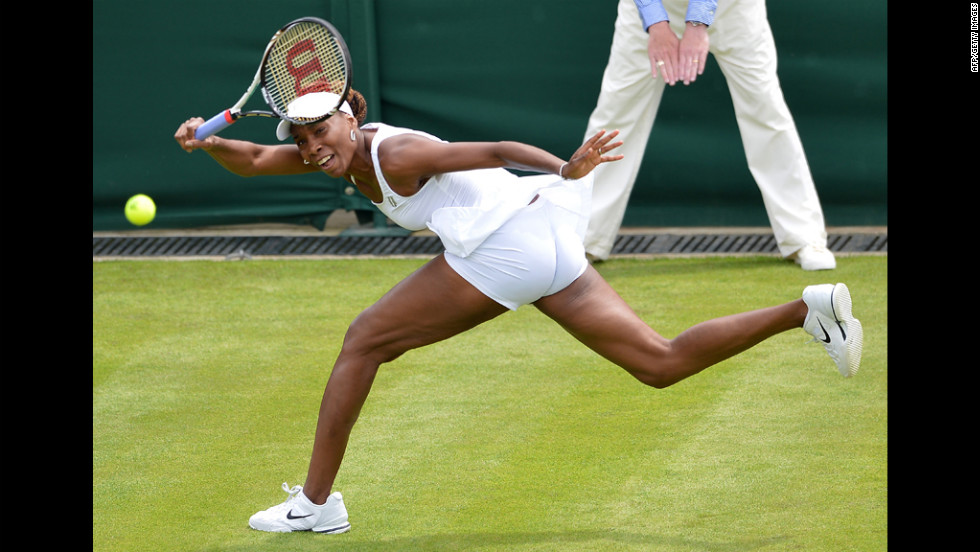 Venus Williams plays a shot during her first-round match against Russia's Elena Vesnina on June 25. Williams lost the match, her earliest exit from the tournament in 15 years.