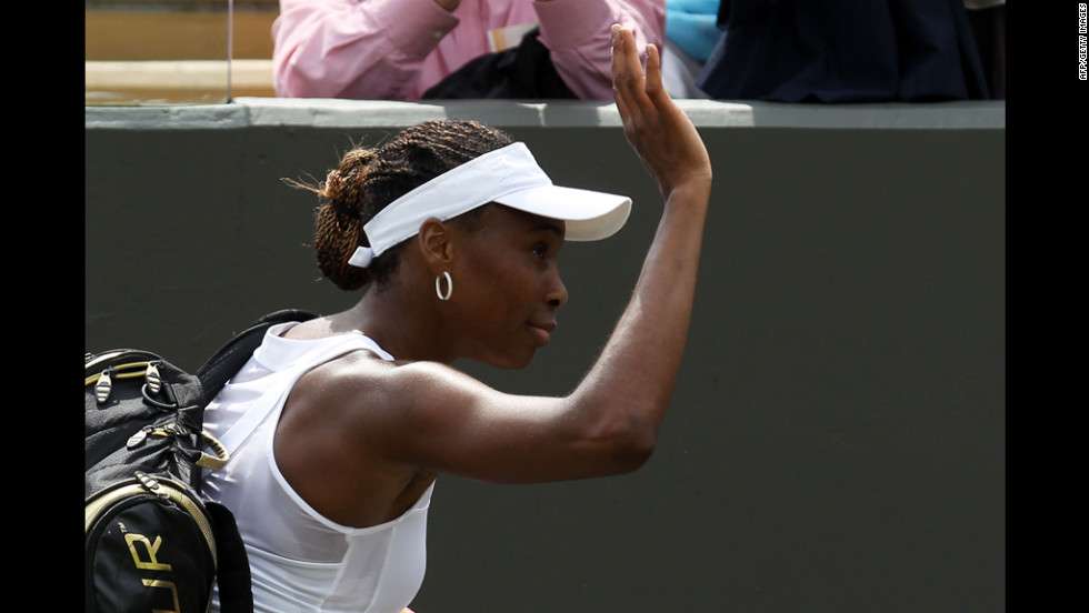 A dejected Williams waves to the crowd after her first-round loss on June 25.