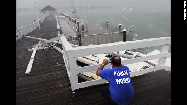Tim Change, from Bradenton Beach Public Works Dept., photographs damage caused by boats breaking free from their moorings and slamming into a pier.