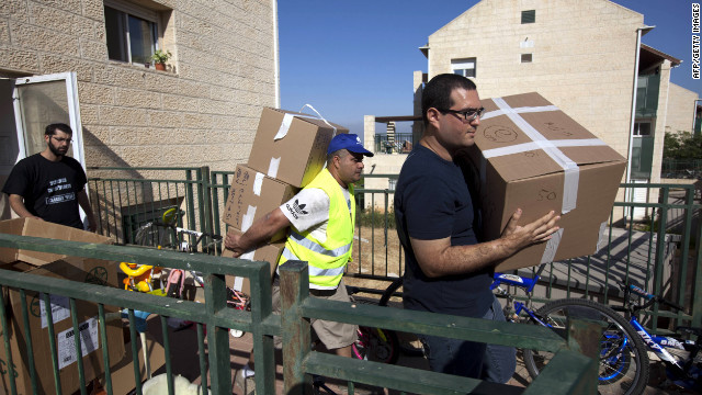 Israeli settlers carry boxes of belongings from houses at the West Bank settlement of Beit El on Wednesday.