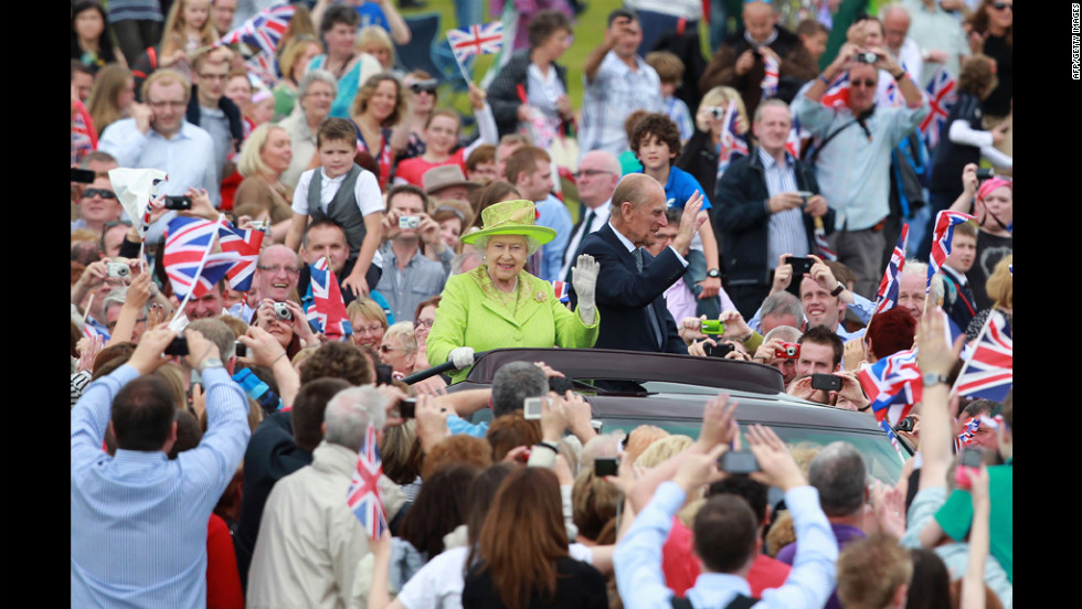 Queen Elizabeth II and Prince Phillip ride through the streets of Belfast, Northern Ireland, on Wednesday, June 27, surrounded by supporters.
