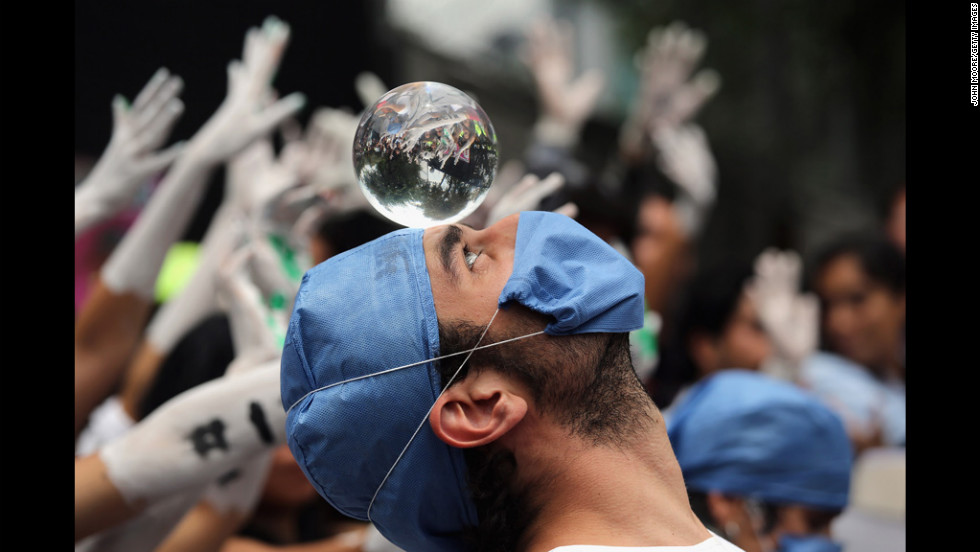 A student protester looks into a crystal ball during a demonstration Tuesday in front of Mexico's Federal Election Commission in Mexico City. Protesters are demanding transparency in elections.