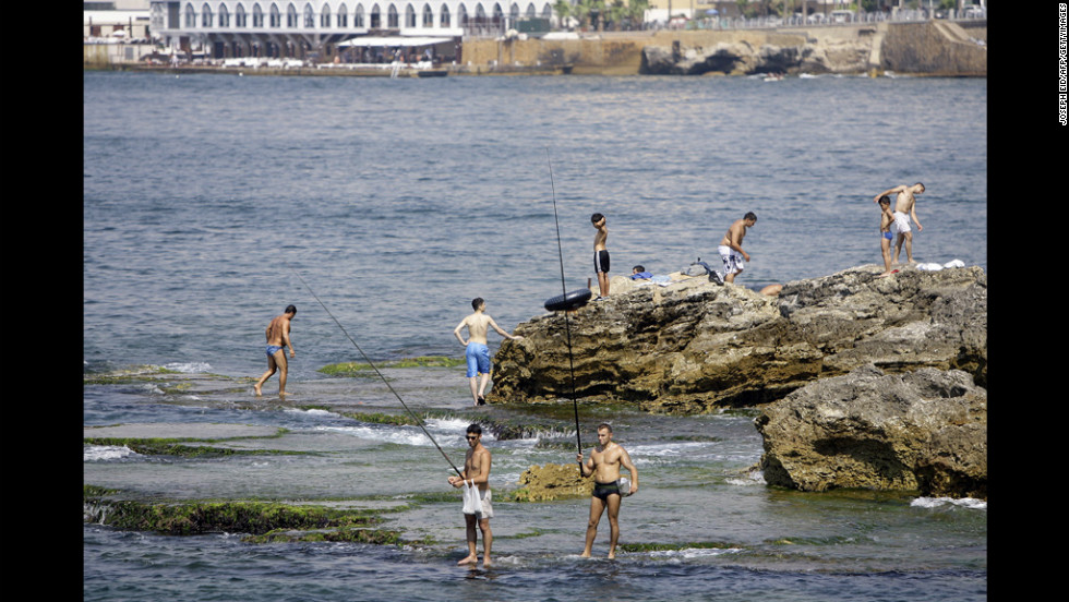 Lebanese men enjoy the day fishing Wednesday at a beach along the Mediterranean Sea in Beirut.
